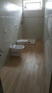 seconda immagine del bagno in fase di ultimazione. Fornitura e posa dei sanitari in appoggio in ceramica bianca, fornitura e posa pavimento in  gres porcellanato